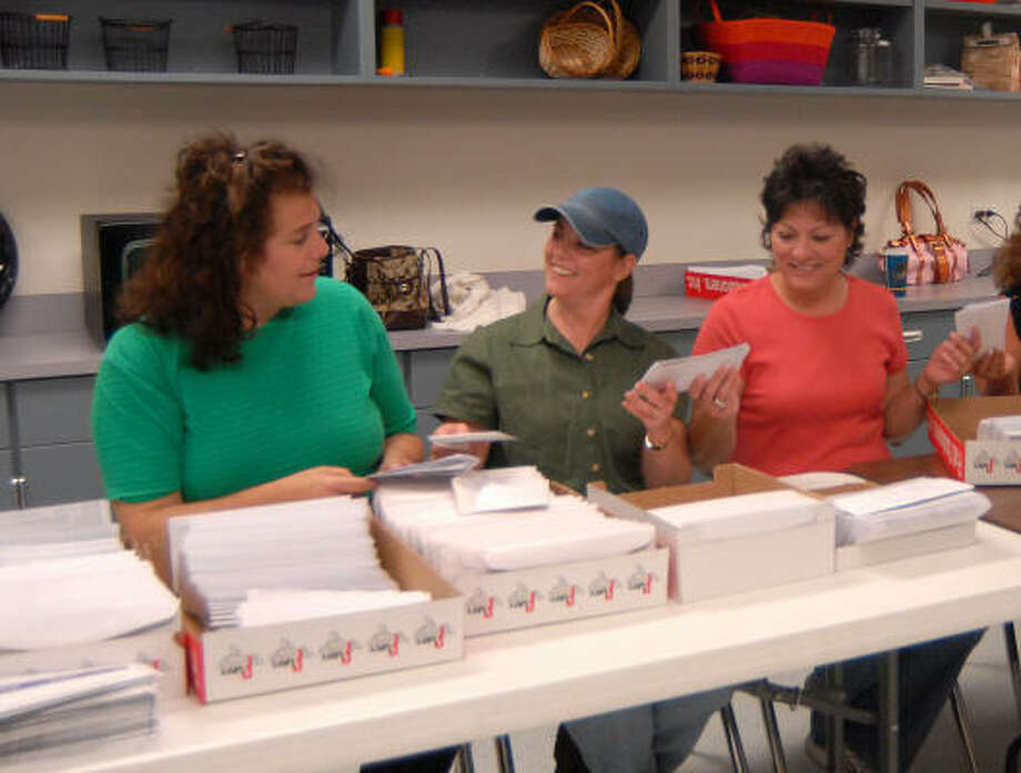 PTO volunteers Suzanne Wassermann, left, Debbie Patin and Darla Gilchrist fill envelopes with report cards and information letters at Montgomery High School. The Montgomery High School PTO volunteers assist staff and teachers at the school with projects needing extra help. Photo: David Hopper, For The Chronicle