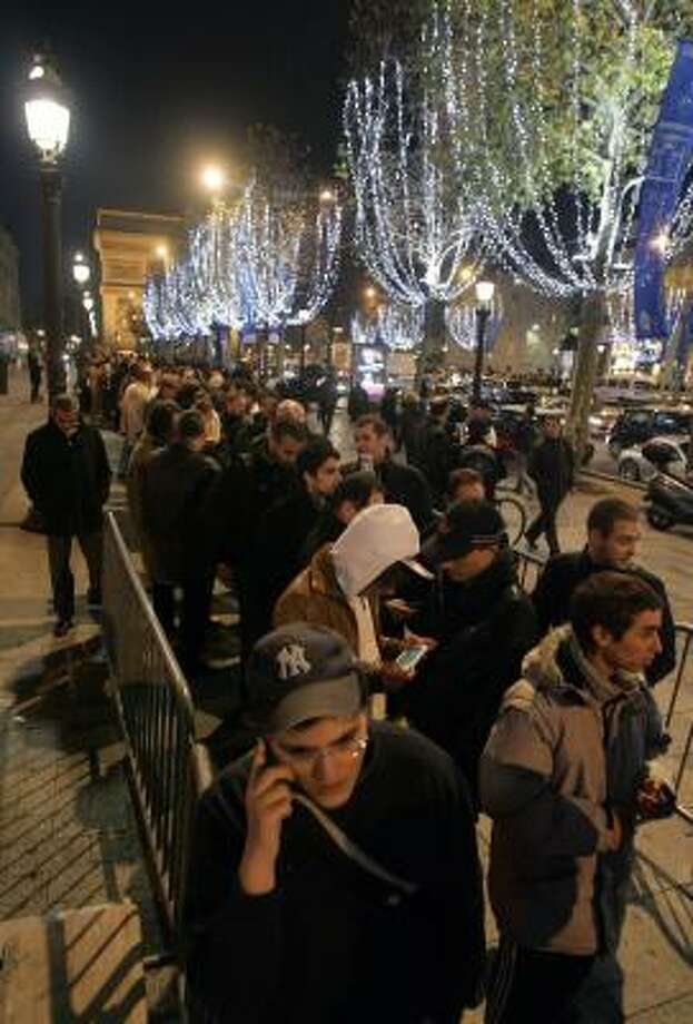Parisians line up on the Champs Elysees on Wednesday to be among the first to purchase an Apple iPhone in France. A faster iPhone is scheduled to debut in the U.S. sometime next year. Photo: REMY DE LA MAUVINIERE, ASSOCIATED PRESS