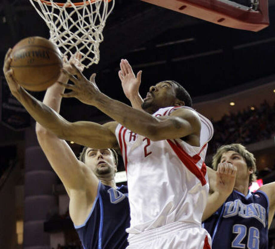 Rockets guard Luther Head, center, goes up for a layup past Utah's Mehmet Okur, left, and Kyle Korver during the second quarter of Game 2. Photo: David J. Phillip, AP