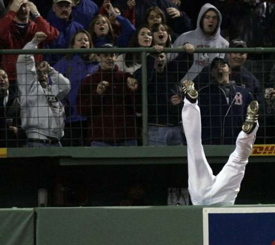 Coco Crisp goes over the wall and into the bullpen trying to catch a home run hit by the Yankees' Alex Rodriguez during the fifth inning of Friday's game at Fenway Park. Photo: CHARLES KRUPA, ASSOCIATED PRESS