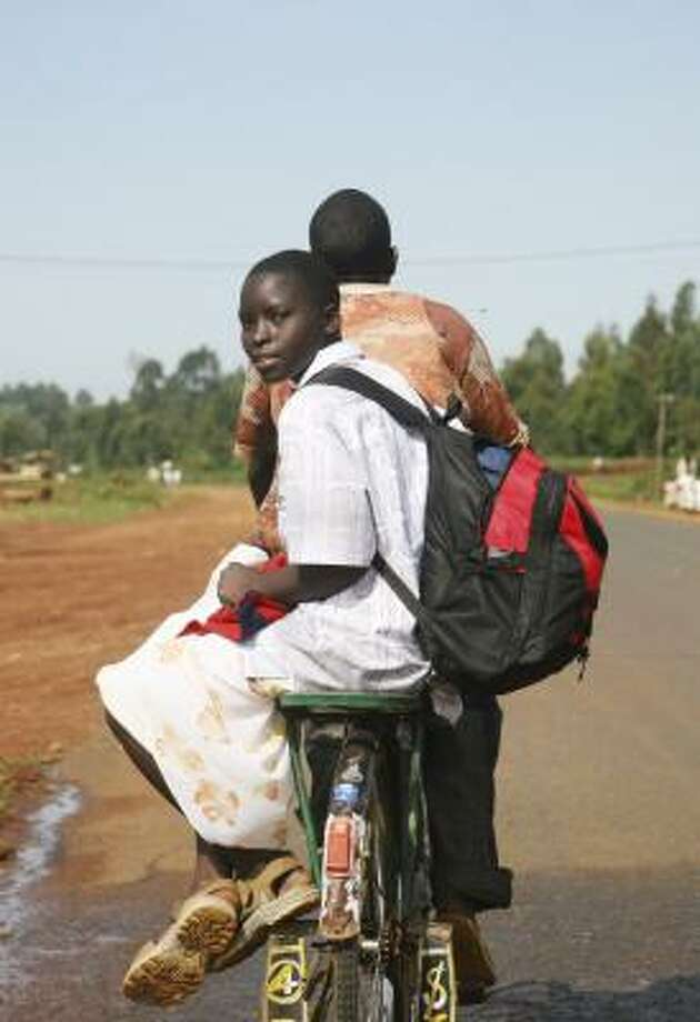 A Kenyan girl rides on a bicycle taxi in Bungoma. Children are finding themselves caught between militias and the military. Photo: KATHARINE HOURELD, ASSOCIATED PRESS