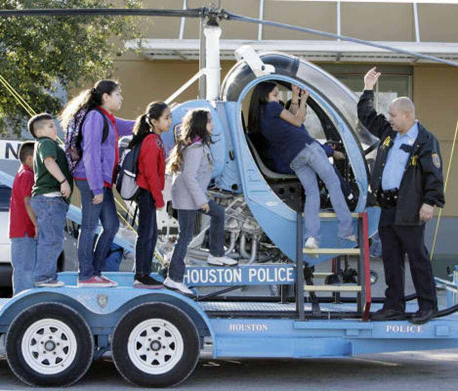 Houston Police officer Anthony Valle shows student members of the Shell Unit of the Boys and Girls Clubs of Greater Houston on Airline Drive a vintage, out-of-service Houston Police Department helicopter that he had trucked to the site. Photo: Billy Smith II, Chronicle