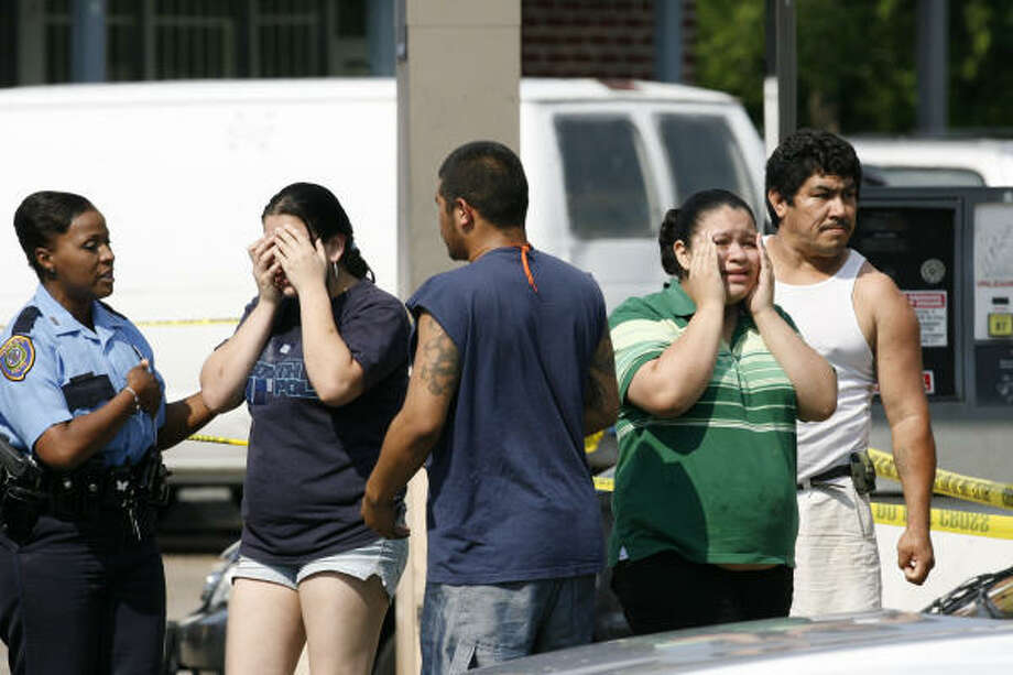 Members of the Houston Police Department console family members of a robbery suspect that was shot dead by police after a short chase in the Bel-Lindo Apartments in the 6100 block of  West Bellfort Saturday. Photo: Billy Smith II, CHRONICLE