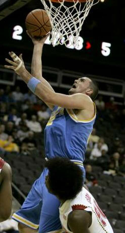 UCLA's Kevin Love scores over Maryland's Bambale Osby. Photo: CHARLIE RIEDEL, AP