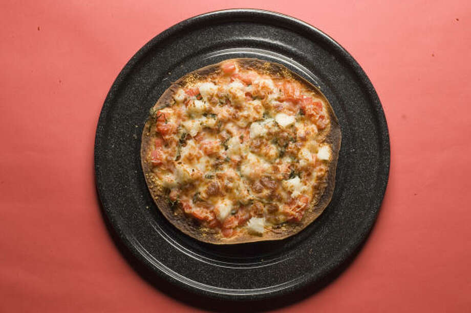 SEAFOOD SNACK: A large flour tortilla - topped with lobster meat, cheese and tomatoes - becomes the crust in this recipe for Red Lobster Lobster Pizza. Photo: Buster Dean, Chronicle