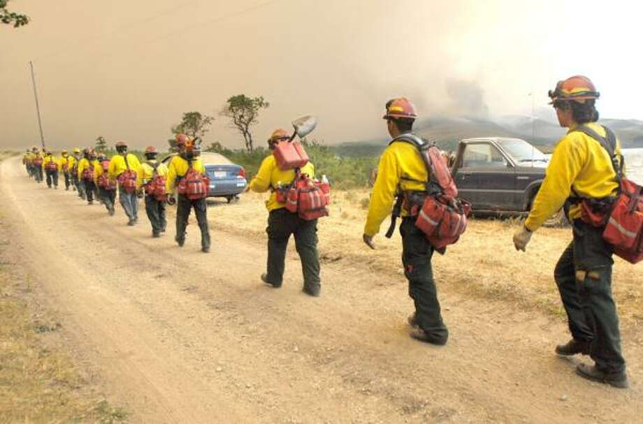 Members of a firefighting team from Kennewick, Wash., march past evacuee Del Hoyt's truck Tuesday into the smoke from the Skyland fire surrounding Dog Gun Lake near East Glacier, Mont. Photo: KRISTINE PAULSEN, (KALISPELL) DAILY INTER LAKE
