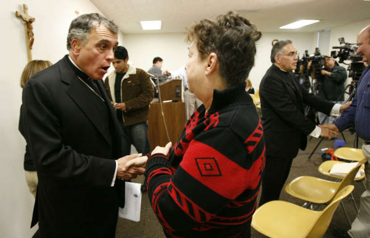 Cardinal Daniel DiNardo speaks with parishoner Marie Flickinger after a Sunday news conference about a sexual-abuse claim against her former pastor, the Rev. Stephen R. Horn. Auxiliary Bishop Joe S. Vasquez is seen at the right.