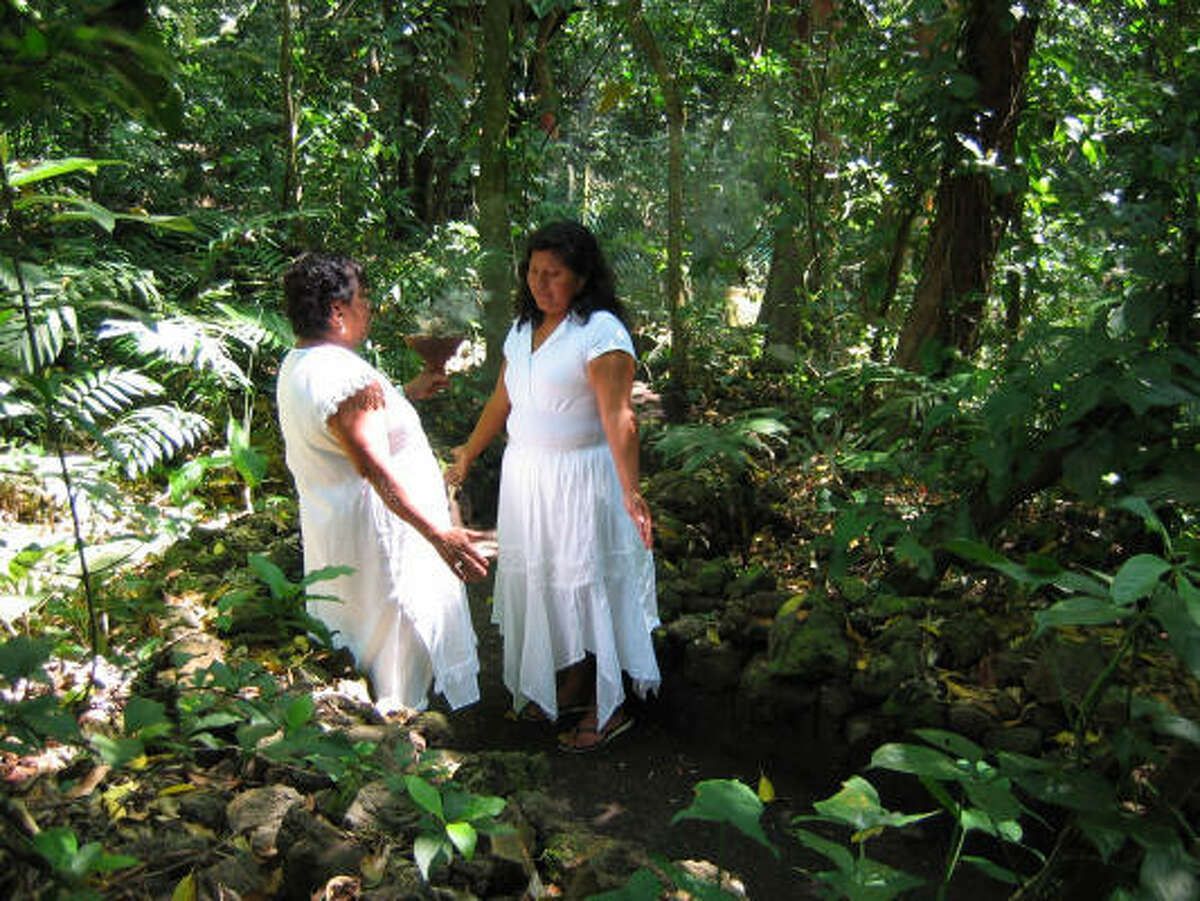 Shaman Asunción Ixtepán, left, and her apprentice pray to Mother Earth and spirits of the trees and plants in a deeply wooded part of Los Tuxtlas.