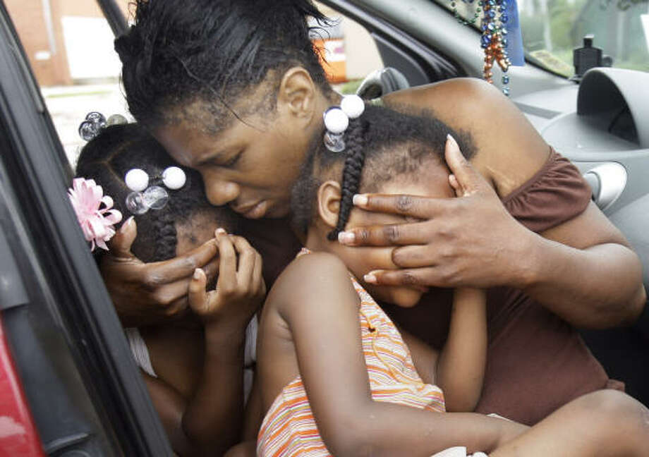 Evacuee Debra Peterson comforts her granddaughters in Slidell, La., as they wait in their car to return to New Orleans on Tuesday. Photo: Eric Gay, Associated Press