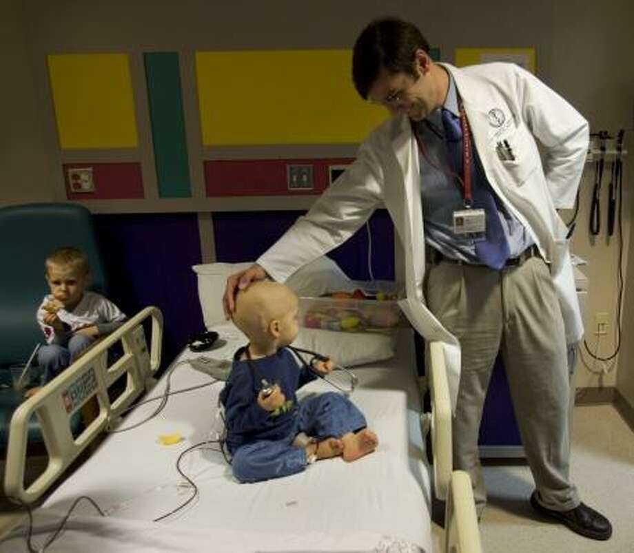 Dr. Maurizio Ghisoli checks on brain tumor patient Nathan Stovall, 2, of Fort Smith, Ark., on Tuesday at M.D. Anderson Cancer Center in Houston. Nathan's brother Ethan is at left. Photo: BRETT COOMER, CHRONICLE