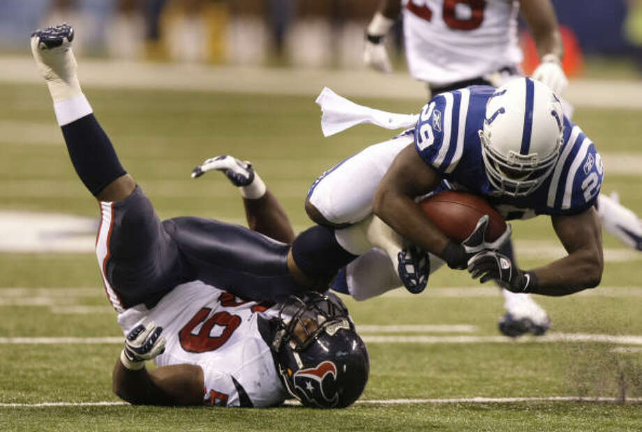 Indianapolis running back Joseph Addai (29) dives over the top of Texans linebacker DeMeco Ryans for extra yardage in the second quarter Sunday. Ryans had 11 tackles but none behind the line of scrimmage. Photo: Brett Coomer, Chronicle