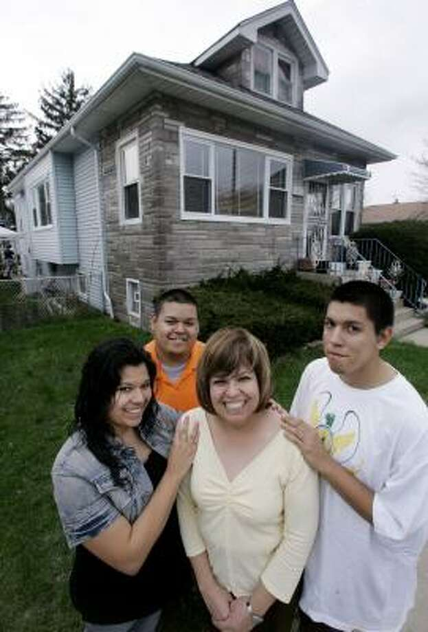 Ana Rodriguez and children Micaela, left, Roberto and Ricardo were able to keep their Chicago home by modifying their home loan. Photo: M. SPENCER GREEN, ASSOCIATED PRESS