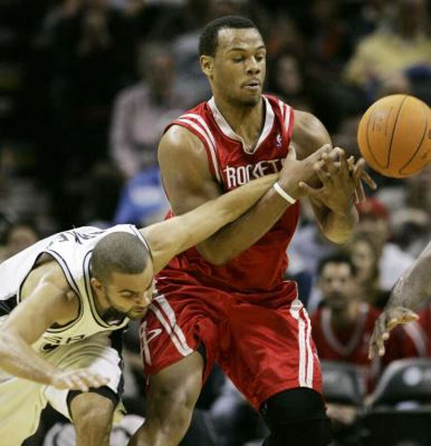 Tony Parker and Chuck Hayes go after the ball during the second quarter. Photo: Eric Gay, AP