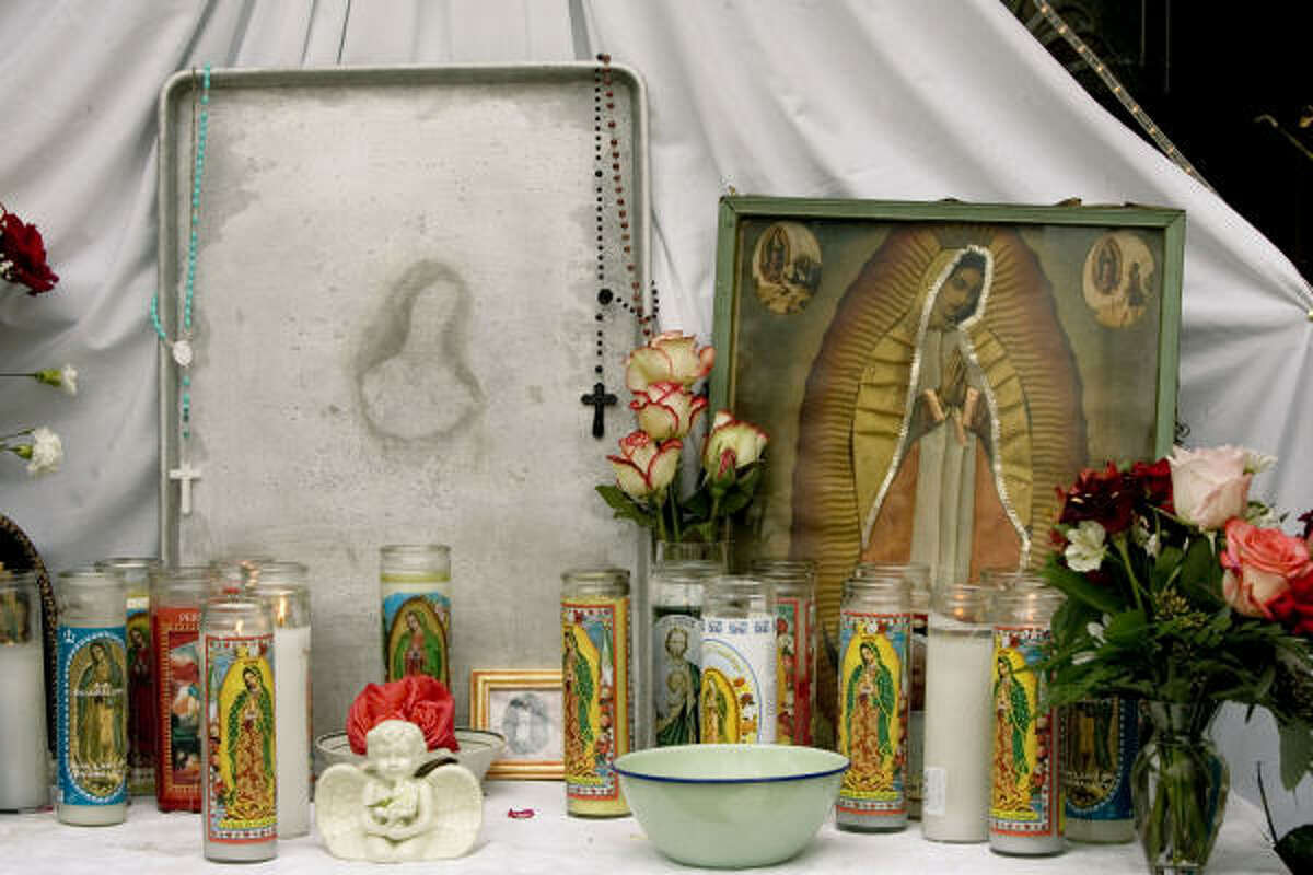 A shrine dedicated to an image bearing the likeness of the Virgin Mary that appeared on a baking pan is shown Friday. The cooking sheet is now on display in the front yard of a home a few blocks away from the school.