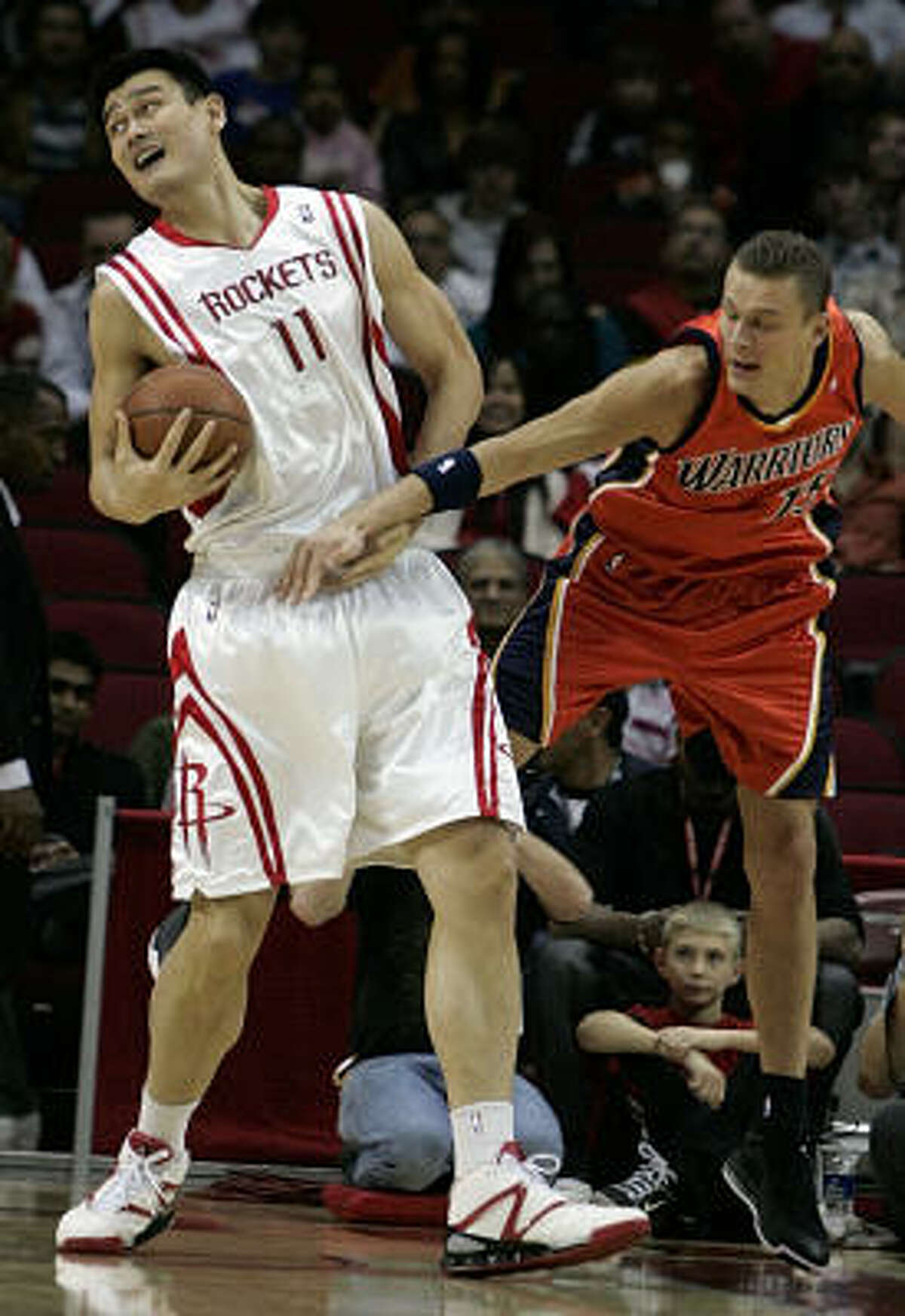 Warriors center Andris Biedrins, right, tries to slow down Yao Ming on his way to the basket in the first half.