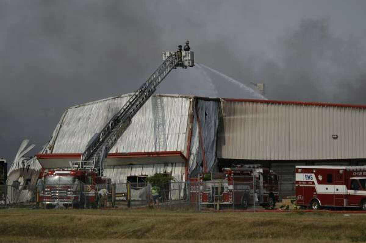 Firefighters battle a four-alarm blaza at the Ram Chemical and Supply warehouse on Greenhouse Road Saturday.