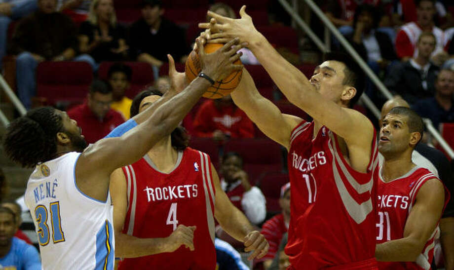 Yao Ming, wrestling for control with the Nuggets' Nene, left, produced 14 points in 22 minutes Saturday. Photo: Smiley N. Pool, Chronicle