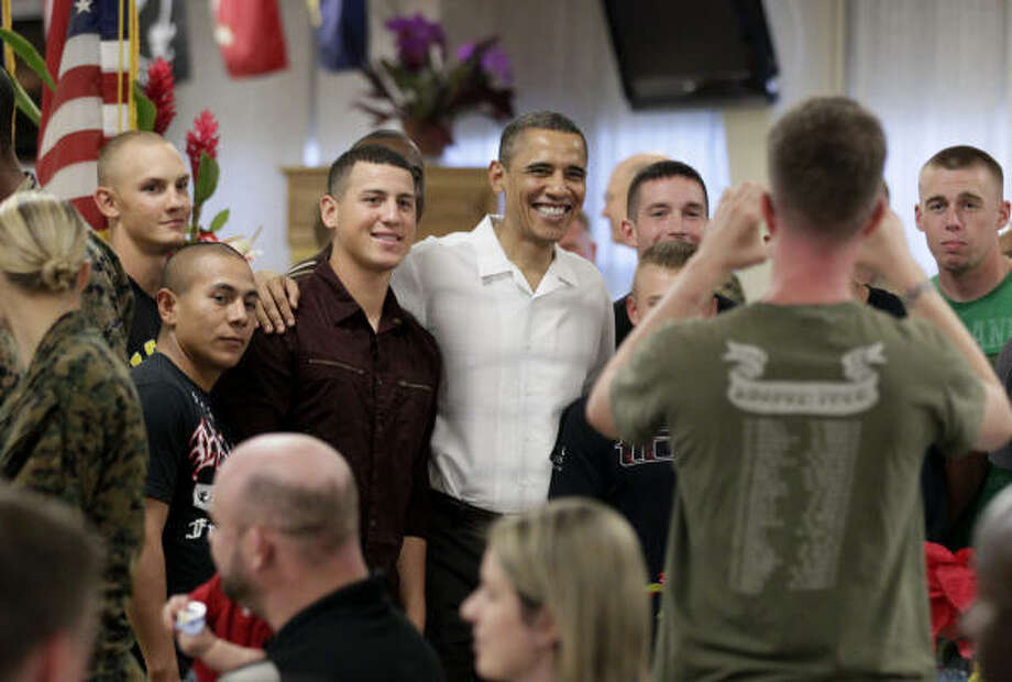 President Barack Obama poses for photographs with members of the military during Christmas dinner at Anderson Hall on Marine Corps Base Hawaii in Kaneohe on Saturday. Photo: Carolyn Kaster, Associated Press