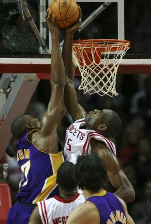Lakers rookie Andrew Bynum, left, learns to deal with rejection at the hands of Dikembe Mutombo. Photo: KAREN WARREN, Houston Chronicle