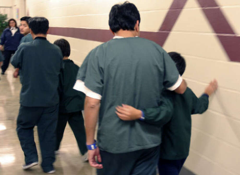 In this image provided by the Department of Homeland Security, immigrant family detainees walk down the hall at the T. Don Hutto Residential Center on Friday in Taylor. The detention facility houses immigrant families awaiting deportation. Photo: Charles Reed, Department Of Homeland Security