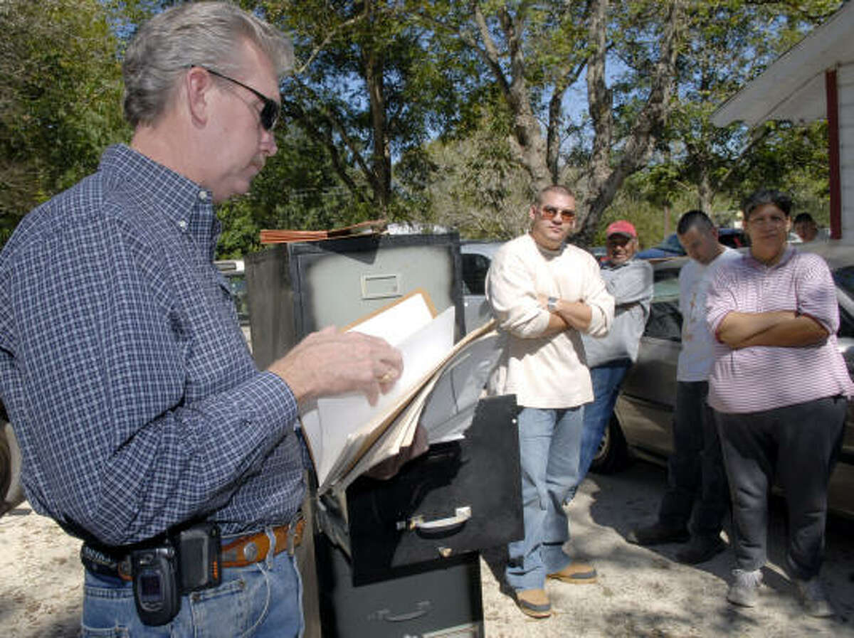Alvin Police Chief Mike Merkel looks over the files that were found in a house that the Moreno family moved into as the Moreno family looks on before the cabinet was removed and taken to the Alvin Police Department, 10/26/07 in Alvin.