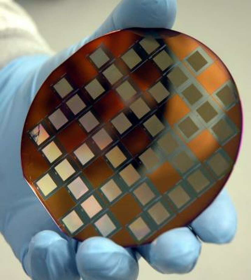 A researcher shows a prototype disk from Cornell University's NanoScale Science and Technology Facility. Photo: KEVIN RIVOLI, ASSOCIATED PRESS