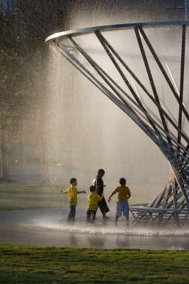 "Kids enjoy a fountain at the new Discovery Green. Titled ""Mist Tree,"" the fountain was donated by Fayez Sarofim. Photo: R. Clayton McKee, For The Chronicle"