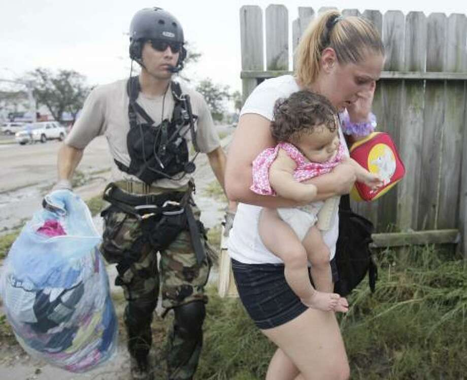 Ellie Cox carries her 6-month-old daughter, Jazya, as an unidentified California National Guardsman helps them to a helicopter Saturday in Galveston. Guard personnel were evacuating people off the island to Texas City High School. Photo: MELISSA PHILLIP, CHRONICLE