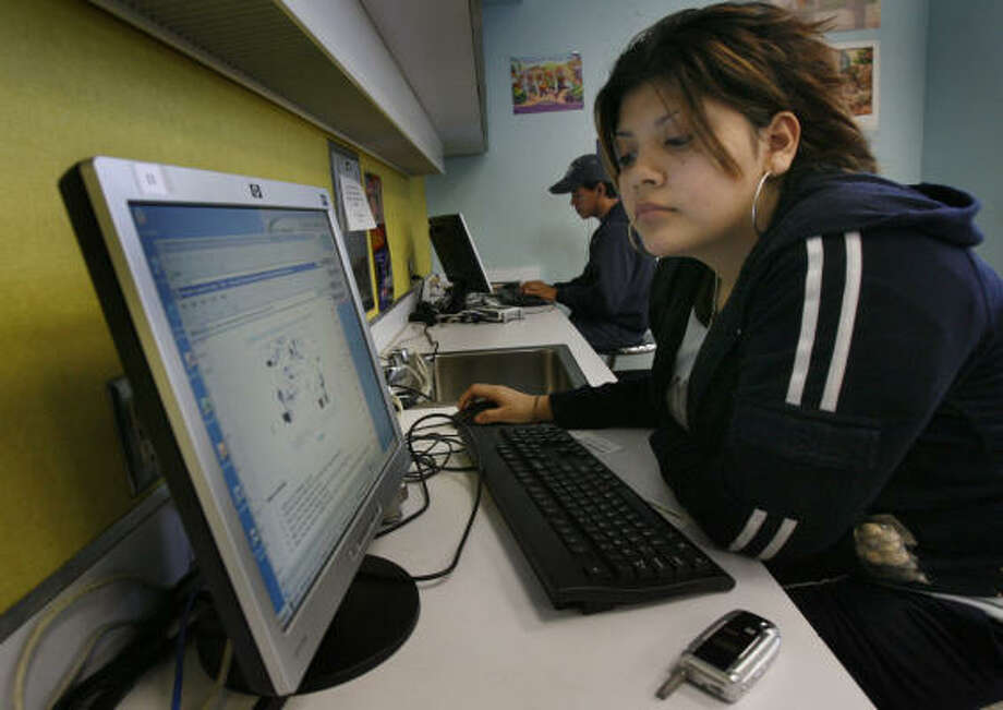 Mireya Zenil, 17, surfs the Web from a computer at Stanaker Library. Zenil began using the library's computers after her family discontinued their home Internet service because of the cost. Photo: Carlos Antonio Rios, Chronicle
