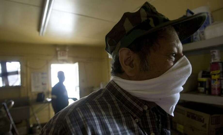 Emilio Calderon covers his nose with a makeshift mask on Thursday as he works to help a friend clean the kitchen at the Taco House restaurant. He wore the mask because of the smell of spoiled food. Photo: JOHNNY HANSON, CHRONICLE