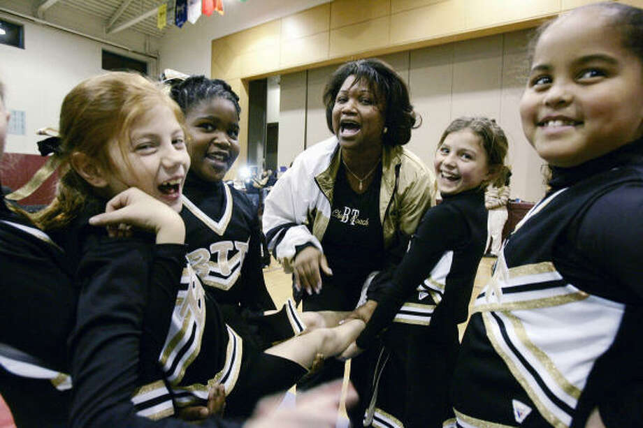 Danica Dilligard, center, an audit manager at Ernst & Young, talks to the cheerleaders she coaches at a New Jersey middle school. Dilligard was coaxed to return to her old job three years after she left. Photo: Mel Evans, AP