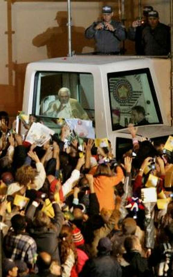 """Pope Benedict XVI arrives in Sao Paulo, Brazil, where thousands waited in the cold rain for a glimpse of him. They chanted """"Bento, Bento"""" and waved flags of different South American nations as he blessed them at the monastery where he is staying. Photo: MARCOS FERNANDES, ASSOCIATED PRESS"""
