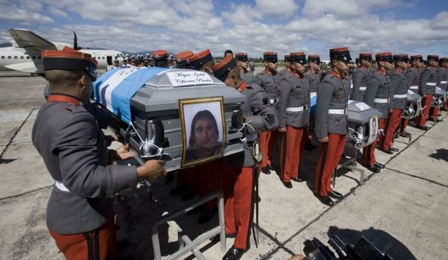 Soldiers carry coffins of eight slain Guatemalan migrants Friday at a base in Guatemala City. Eleven Guatemalans and 61 Central and South American migrants were massacred by drug cartel gunmen at a ranch in the Mexican northern state of Tamaulipas. Photo: Moises Castillo, AP