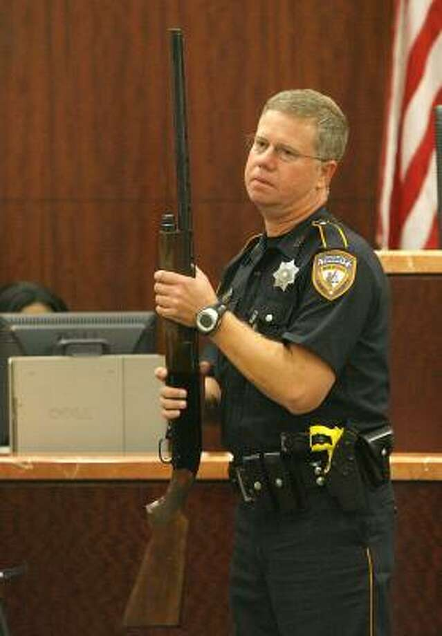 A bailiff takes charge of a shotgun that was used as evidence Wednesday in the trial of David Mark Temple. Temple's brother denies he was ever threatened with a shotgun by the defendant. Photo: STEVE CAMPBELL, CHRONICLE