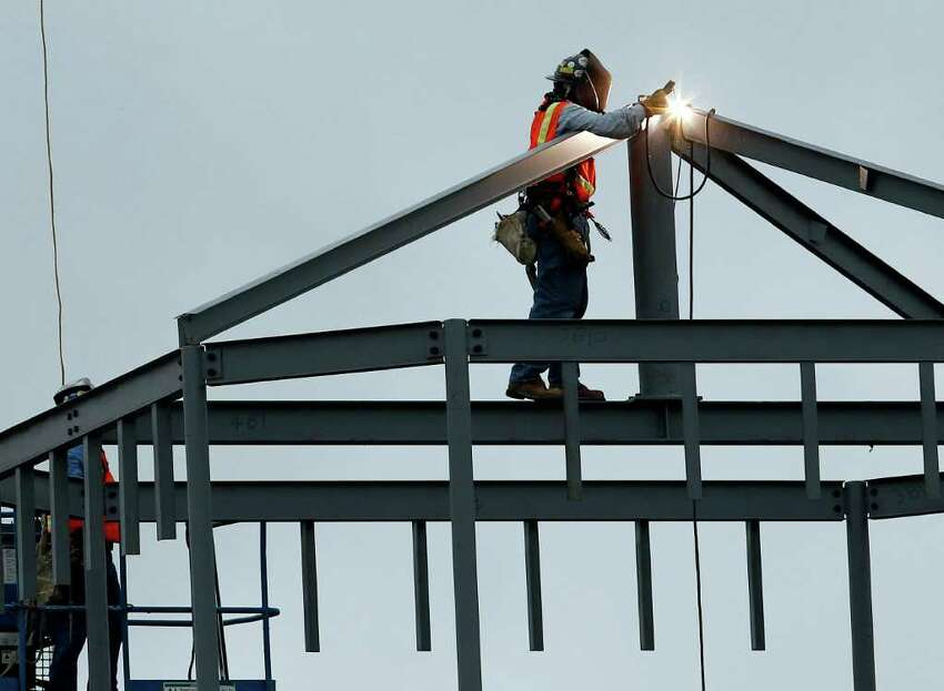 A worker welds steal beams at a constructions site, Thursday, July 21, 2011, in San Antonio. Excessive heat continues across much of the U.S.