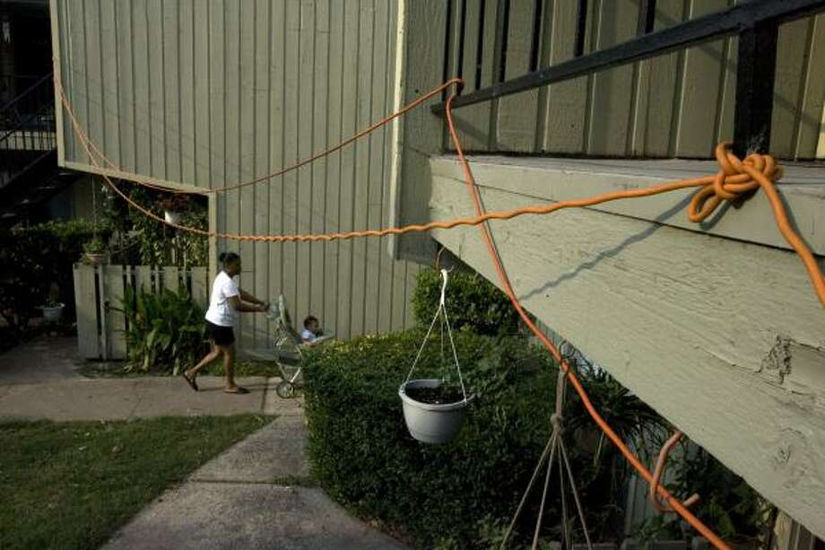 At the Oakwood Gardens apartment complex in northwest Houston, residents whose power has been restored use electrical cords to share their good fortune with those still living in the dark. Photo: JOHNNY HANSON, CHRONICLE