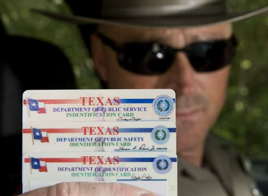 Can you spot the legitimate identification card State Trooper Todd Box is holding? The fake cards, which misidentify the Texas Department of Public Safety, are on the top and bottom. Photo: BRETT COOMER, CHRONICLE