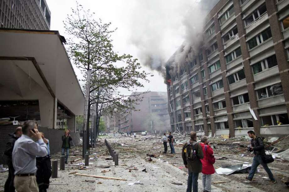 People make phone calls as they stand near a burning government building in Oslo on Friday. Norwegian police confirmed that people were killed and injured in Friday's explosion near government buildings in the capital Oslo.  AFP PHOTO / SCANPIX NORWAY - THOMAS WINJE Photo: THOMAS WINJE, AFP/Getty Images / 2011 AFP