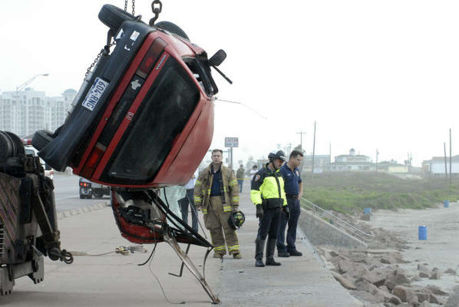 Galveston police and firefighters recover a body that was ejected from a car that plunged off Seawall Boulevard at 13th Street early on Friday. Photo: CARLOS JAVIER SANCHEZ, Chronicle