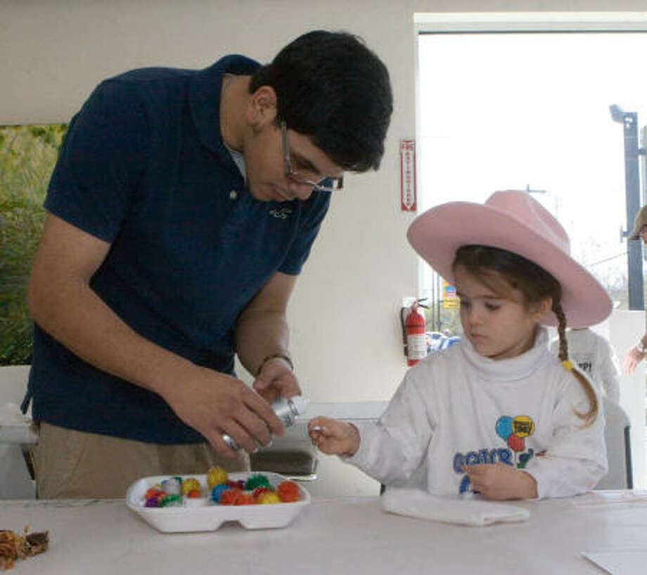 Volunteer Gabriel Montelongo helps Claire Conery, 3 1/2 , with a sock puppet during the Family Open House at the Art League Houston's new building, 1953 Montrose Blvd. Photo: R. Clayton McKee, For The Chronicle