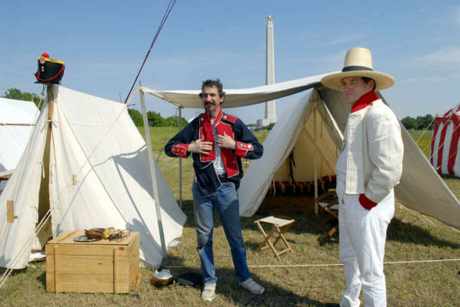 Andy Heilveil puts on a dress uniform as John Tyler looks on from the Mexican campsite at the San Jacinto Monument, as they get ready for the San Jacinto Festival tomorrow. Both men are from Austin. Photo: Kim Christensen, For The Chronicle