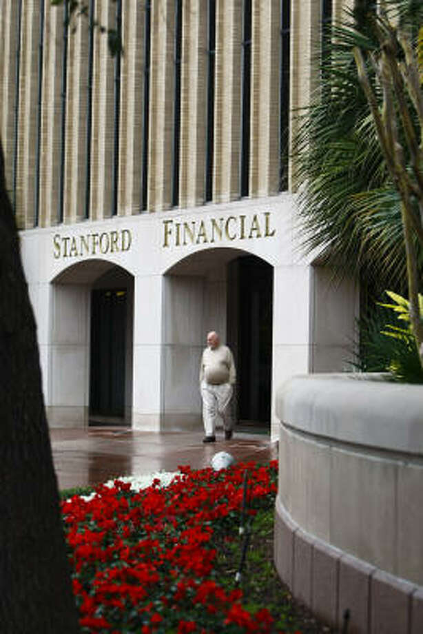 A man walks away from the Stanford Financial Group Building at 5050 Westheimer. Photo: Michael Paulsen :, Chronicle