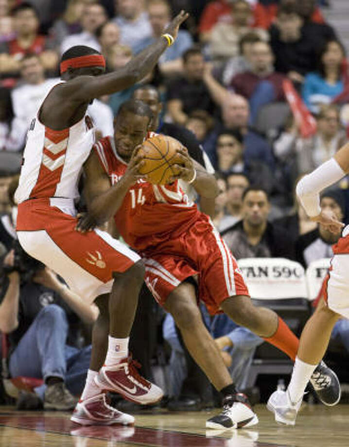 Rockets forward Carl Landry drives into Raptors forward Pops Mensah-Bonsu during the first half. Photo: Frank Gunn, AP