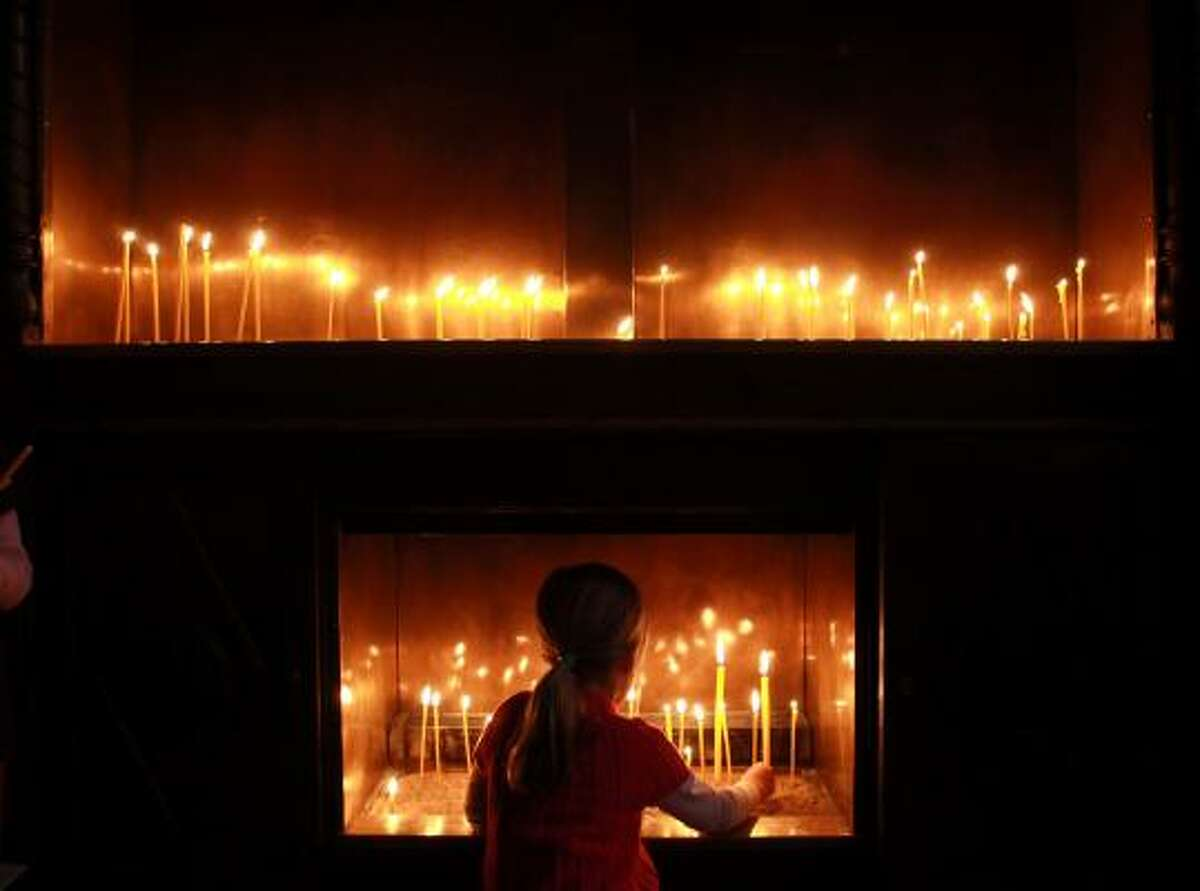 A young woman lights a candle during the Good Friday Mass at a cathedral in Varna, Bulgaria.