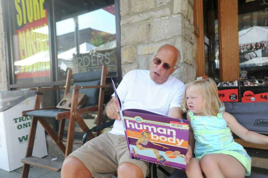 Flint, Mich., resident Michael Melet, left, reads to his granddaughter, 3-year-old Ann Arbor resident Gillian Daly in front of the downtown Borders store on the first day of liquidation in Ann Arbor, Mich., July 22, 2011. Borders Group began liquidation sales at all of its 399 stores as the 40-year-old chain winds down operations. Photo: Angela J. Cesere, AP / AnnArbor.com