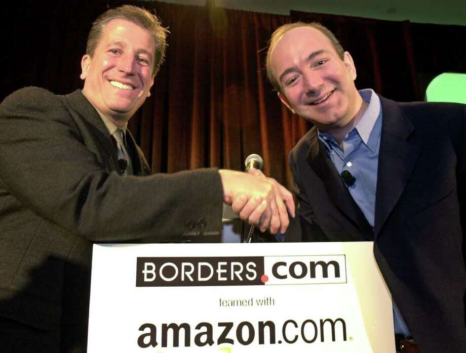 Borders Group President and CEO Greg Josefowicz, left, and Amazon.com founder and CEO Jeff Bezos shake hands after a news conference in New York Wednesday April 11, 2001, announcing that online retailer Amazon.com will take over Borders Group Inc.'s online bookselling operations as part of a new partnership between the two companies. Photo: KATHY WILLENS, AP / AP