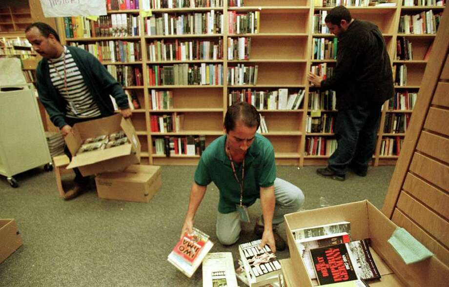 """Employees of the $2.6 billion American bookstore giant, Borders, unload boxes and fill bookshelves at a new store in San Juan, Puerto Rico, Monday Feb. 7, 2000. Borders has chosen this Spanish-speaking U.S. Caribbean island for its first """"bilingual"""" superstore. (AP Photo/Ricrdo Figueroa)    Photo: RICARDO FIGUEROA, AP / AP"""