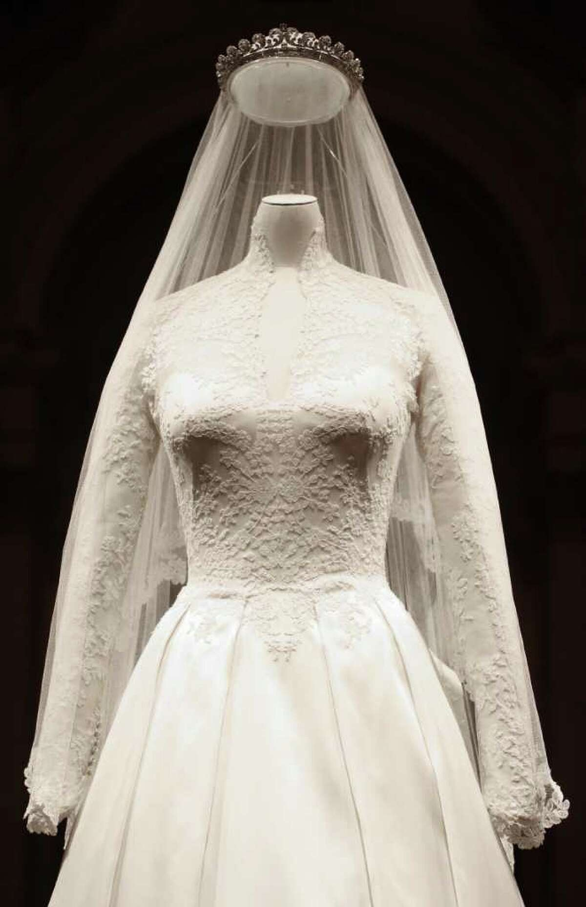 The Duchess of Cambridge's wedding dress, designed by Sarah Burton for Alexander McQueen, is seen in Buckingham Palace, London, Wednesday July 20, 2011, before going on display to the public during the palace's annual summer opening. The intricately decorated wedding dress received a rapturous reception. For months, it was fashion's best-kept secret. Even the team of embroiderers at Hampton Court Palace working on the gown did not know the identity of the designer until shortly before the public announcement. But as soon as the Duchess appeared leaving the Goring Hotel and then entering Westminster Abbey on her wedding day on April 29, the secret was out. The bridal gown featured lace appliqua floral detail and was made of ivory and white satin gazar, with a skirt that resembled