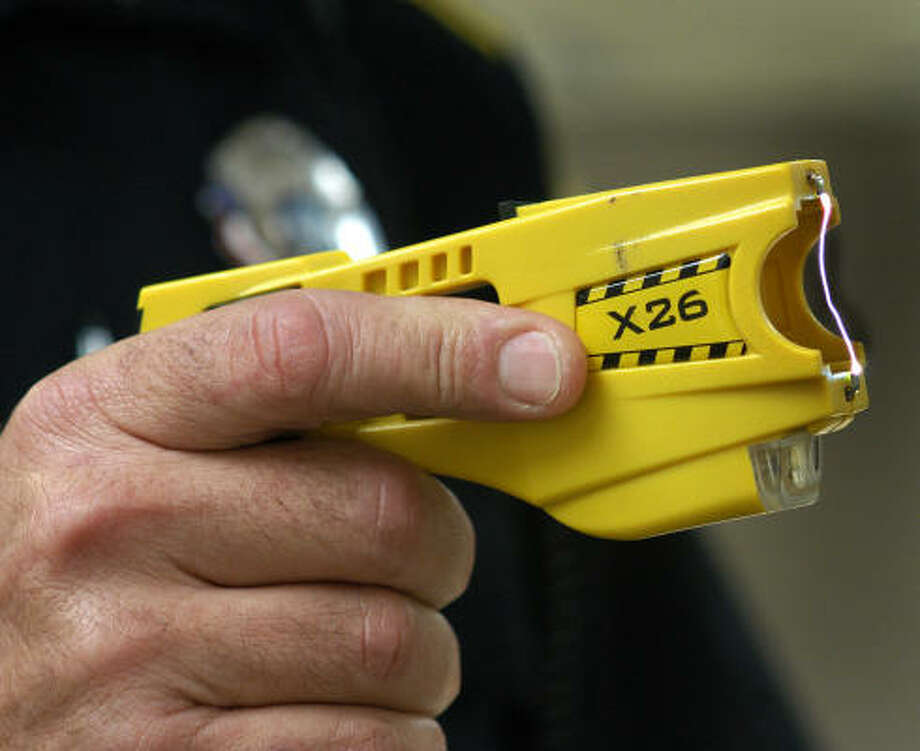A police officer tests the battery of the Taser he carries on duty. Chronicle file photo.