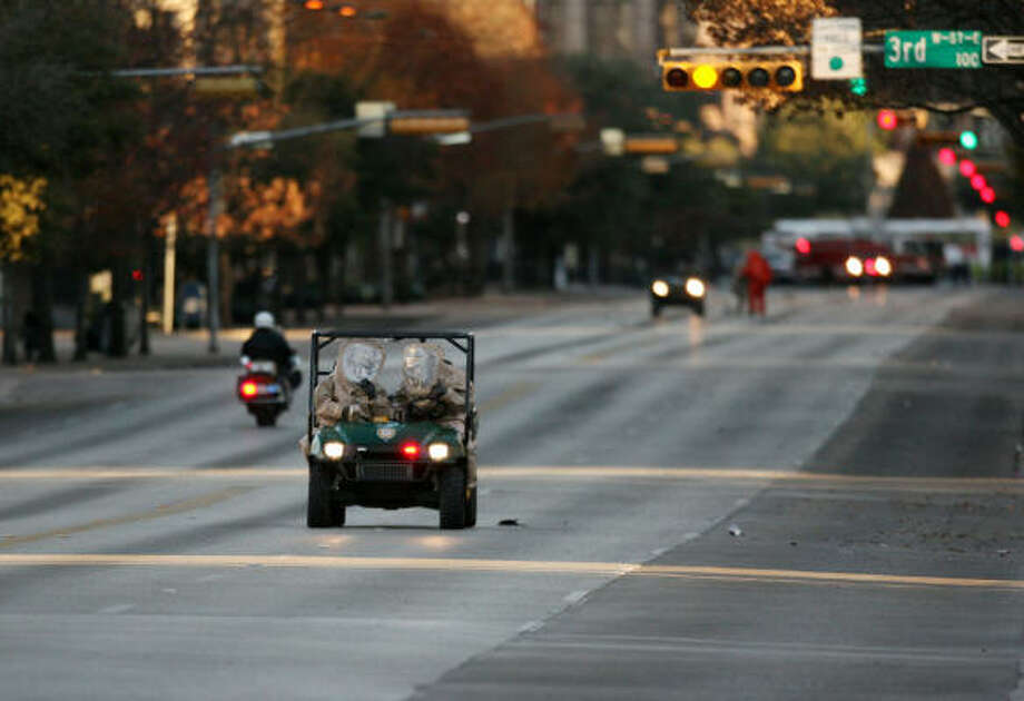 Crews collecting birds are shown on a closed off stretch of Congress Avenue in downtown Austin today. Photo: Brian K. Diggs, AP